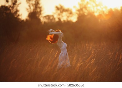 A woman with red curly hair in white sundress on background of dawn. Red-haired girl with pale skin, bright unusual appearance and red lips and thin waist in the field on background of rising sun.