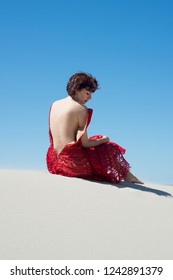 Woman in a red dress with a bare back is sitting on the sand