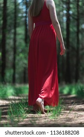 Woman in red dress in bare feet on forest path.