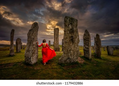 Woman in red dress at Callanish stones in sunset light, Lewis, Scotland