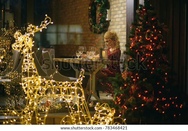 Woman in red dress celebrate new year and christmas. Girl enjoy party food, drinks in restaurant. xmas toast, alcohol, cheers. Festive fashion, style, decorations. Winter holidays celebration concept.