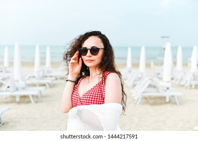 A woman in a red dress and curly hair is standing on the beach. A man with happy emotions. Walk along the sea promenade. Travel and tourism in the summer. Copy space