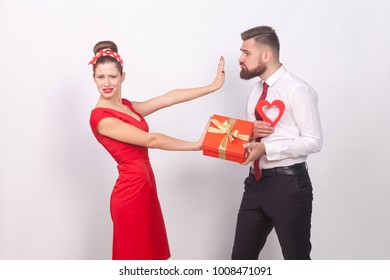 Woman in red dress, don't need present and love. Indoor, studio shot, isolated on gray background