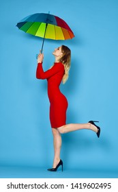 woman in a red dress in full growth holding a colored umbrella on a blue background