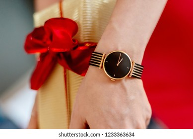 Woman in red dress giving Christmas gift in gold box with red ribbon. Christmas surprise. Merry Christmas!