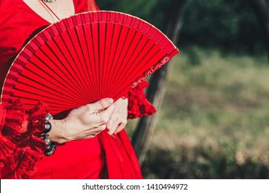 Woman in red dress with hand red open fan and bracelet, headless portrait
