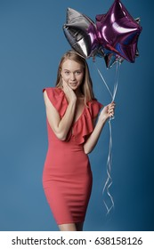 Woman in red dress holding balloons on the blue background