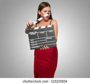Woman In A Red Dress Holding Clapper Board against a grey background