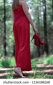 Woman in red dress holding shoes in hand. Standing on forest path.