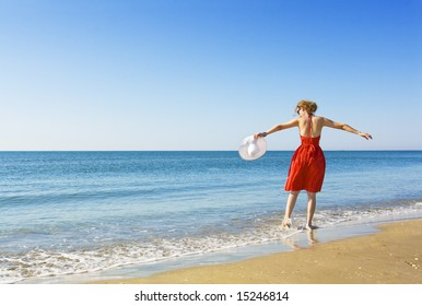 woman in red dress  holding white hat dancing on the beach