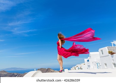 Woman in the red dress looks at the sea from the high roof
