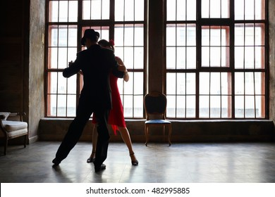 Woman in red dress and man in black suit dance tango near big window in room