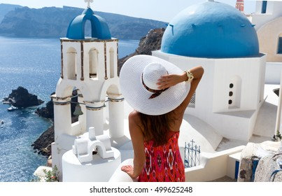 Woman in red dress in Oia, Santorini, in front of a church