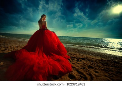 A woman in a red dress on the beach. Maritime vacation. Journey to the sea