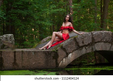 Woman in red dress on bridge in forest