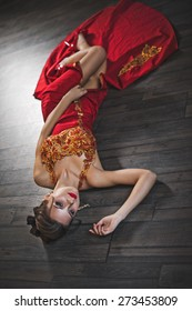 The woman in a red dress on a floor.