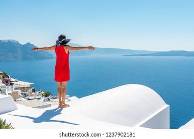 Woman in red dress on the roof enjoying view of Santorini island and Caldera in Aegean sea. Greece.