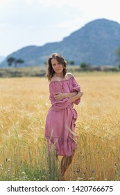 Woman in red dress posing in a wheat field