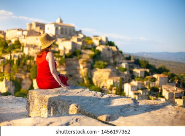Woman in red dress sits back to the camera and enjoys beautiful view of Gordes, old town in Provence. France