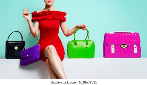 Woman with red dress sitting with many colourful bags.