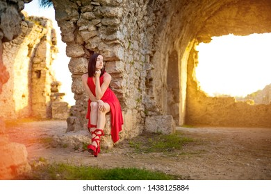 Woman in red dress is sitting at the ruins of an ancient city, Side, Antalya, Turkey