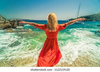 woman in red dress standing on rock by sea