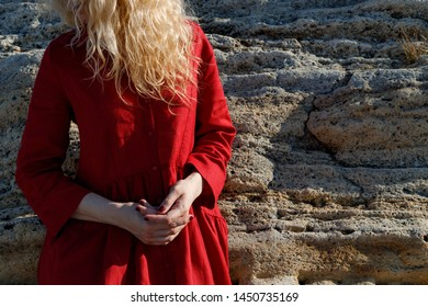 A woman in a red dress is standing on the beach