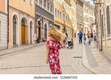 Woman in red dress taking tour in an european town, Goerlitz, Germany