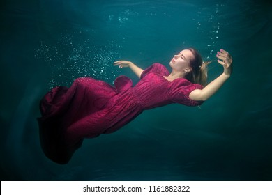 Woman in a red dress is underwater, she is sleeping.