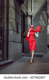 Woman in a red dress is walking around the city.