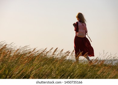 Woman in red dress walks along the seashore at sunrise