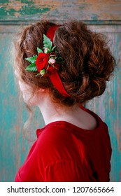 Woman in red dress wearing hair decoration made of roses and fern. Classic wedding hairstyle.