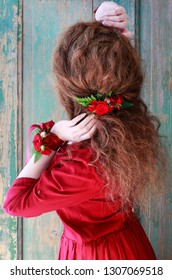 Woman in red dress wearing hair and hand decorations made of roses and fern.