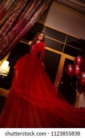 Woman in red evening dress posing on festive background