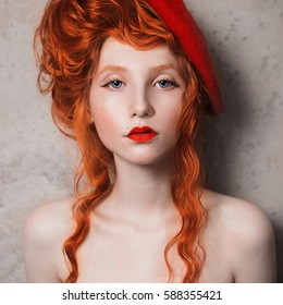 A woman with red hair in a red dress. Red-haired girl with pale skin and blue eyes with a bright unusual appearance with a beret on her head on a gray background. French courtesan. French courtesan