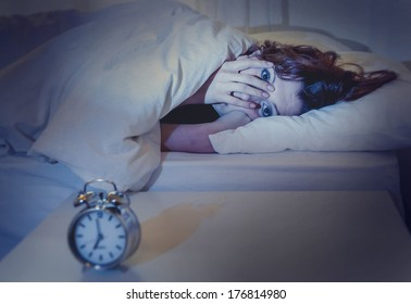 woman with red hair in her bed with insomnia and nightmare can't sleep waiting for her alarm clock to go off on a white background