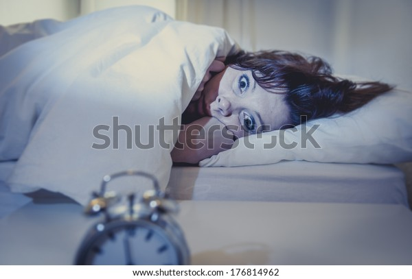 woman with red hair in her bed with insomnia and nightmares can't sleep waiting for her alarm clock to go off on a white background