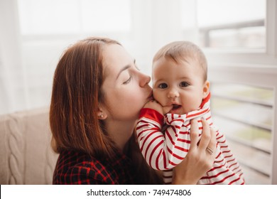 Woman with red hair kisses pretty little boy