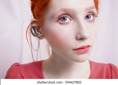 A woman with red hair in an orange dress. Red-haired girl with pale skin, blue eyes, a bright unusual appearance, red lips and earrings on the ear looking at the camera