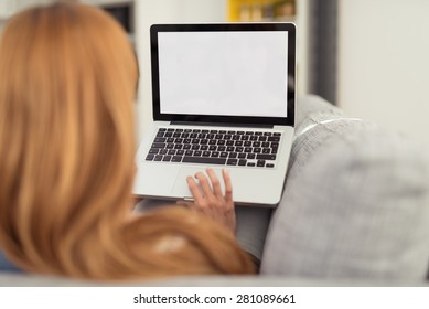 Woman with Red Hair Sitting on Sofa with Laptop Computer, Perspective from Behind Over Shoulder Looking at Blank Computer Screen