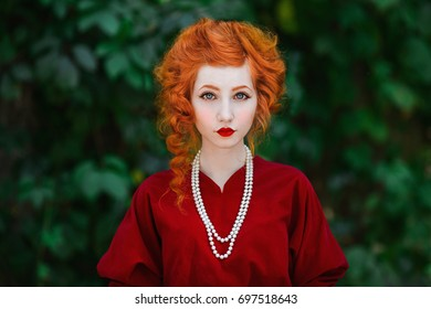 Woman with red hair and red slinky dress posing on a background of green leaves. Red-haired girl with pale skin and blue eyes with a bright unusual appearance with necklace of beads around her neck