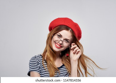 Woman in red hat and glasses smiling fashion.
