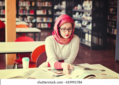 Woman in red headscarf working looking into the book