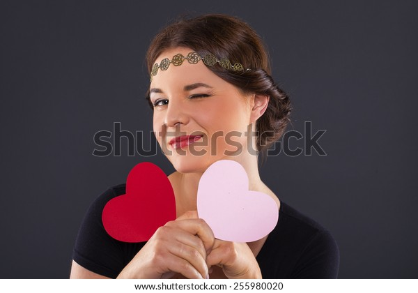 woman with red heart on black background. studio