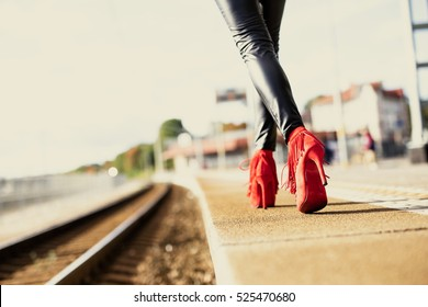 Woman in red high heels walking in train station