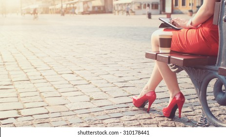 Woman in red high-heeled shoes and dress using digital tablet. Beautiful sexy business woman enjoying sunny morning in the city, sitting on the bench, browsing Internet and drinking coffee. Lens Flare