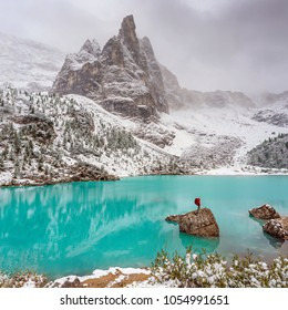 woman in red jacket with knapsack on stone in the middle of mountain lake Lago di Sorapiss in Dolomite Alps. Italy, with amazing turquoise color of water.