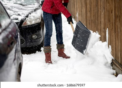 woman in red jacket with shovel cleaning snow. Winter shoveling. Removing snow after blizzard
