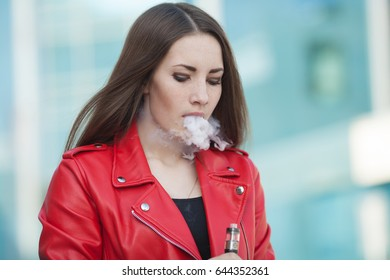 Woman in red jacket vaping hold modern e-cig device mouthpiece in lips.Quit smoking nicotine. Young ejuice smoker woman with electronic cigarette gadget, vaping device.