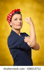 Woman with a  red kerchief and a clenched fist, vintage or retro effect of the 40s in America, yellow background, copyspace, sign for women power